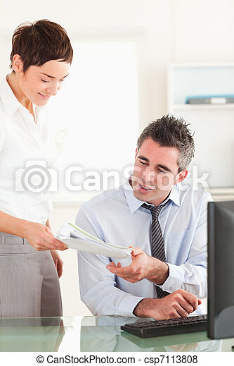 Portrait of a manager receiving a document from his employee - csp7113808