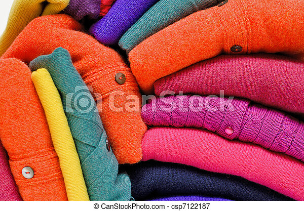 Stack of women's sweaters and cardigans in bright vivid colours against white. - csp7122187