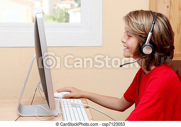 child with headphones or earphones listening to music or chatting on home or school pc computer - csp7123053