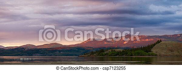 Distant Yukon mountains glowing in sunset light - csp7123255