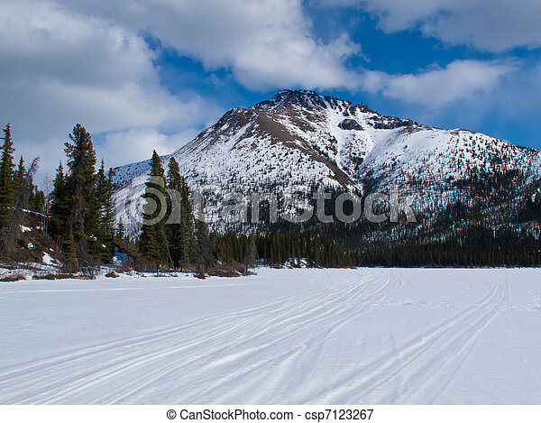 Well used winter trail on frozen mountain lake - csp7123267