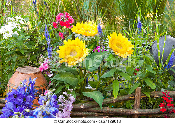 Rural pot on a wattled fence with a sunflower and wild flowers - csp7129013