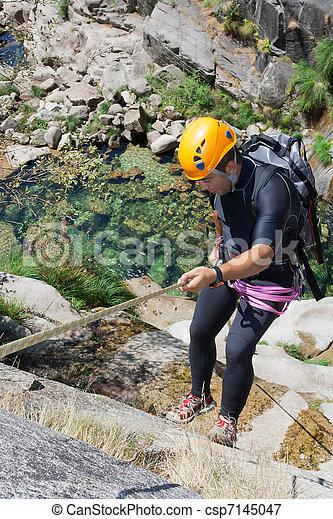 Men descending waterfall - csp7145047