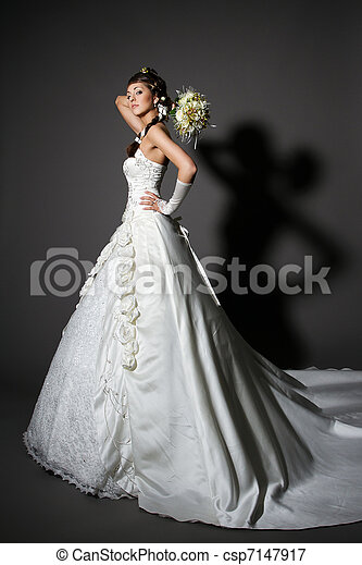 Bride in white elegance wedding dress with tail. Hand rised up with bouquet. Full length. - csp7147917