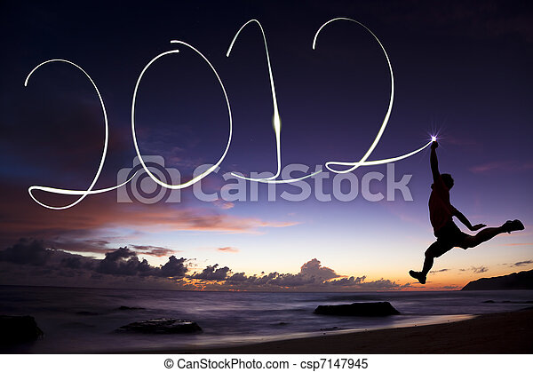 happy new year 2012. young man jumping and drawing 2012 by flashlight in the air on the beach before sunrise - csp7147945