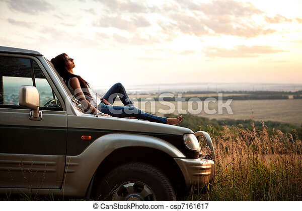 woman is laying on the car's hood - csp7161617