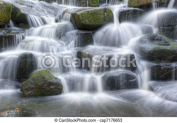 Beautiful waterfall cascades over rocks in lush forest landscape - csp7176653