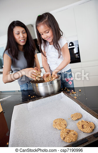 Mother and Daughter Baking Cookies - csp7190996