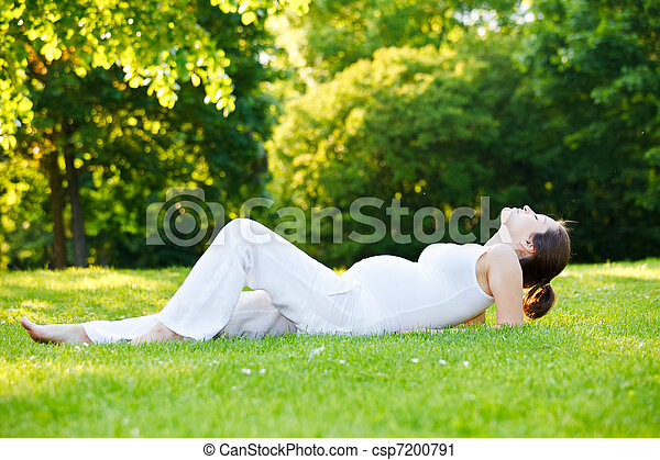 Beautiful pregnant woman relaxing in the park - csp7200791
