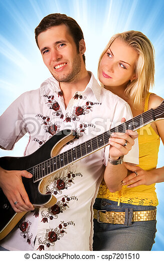 Young musician plays guitar and beautiful blond girl stands nearby - csp7201510