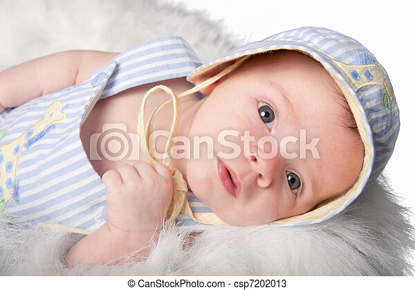 Curious baby boy in hat stares ahead - csp7202013