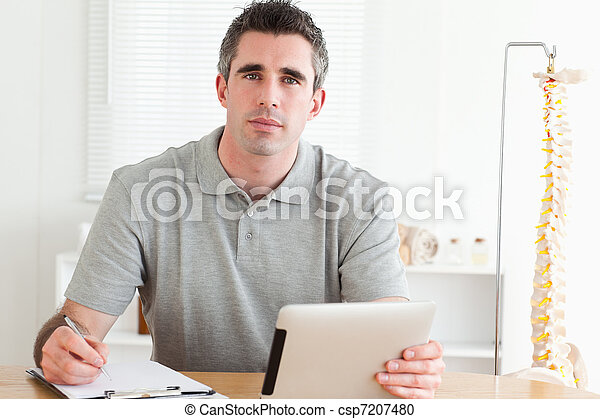 Male Doctor working with a tablet and a chart - csp7207480