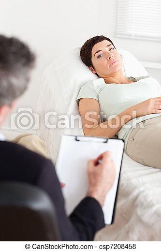 Psychologist talking to a sad female patient - csp7208458
