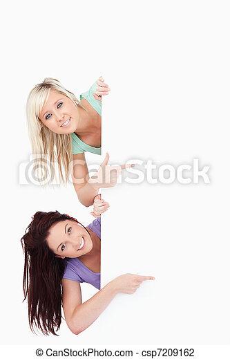Cute Women peeking around a banner showing copyspace - csp7209162