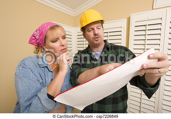 Contractor in Hard Hat Discussing Plans with Woman - csp7226849