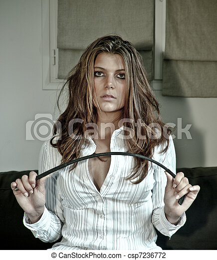 Provocative girl on sofa with horsewhip - csp7236772