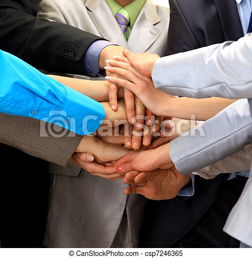 group of business people making a pile of hands in a light and modern office environment - csp7246365
