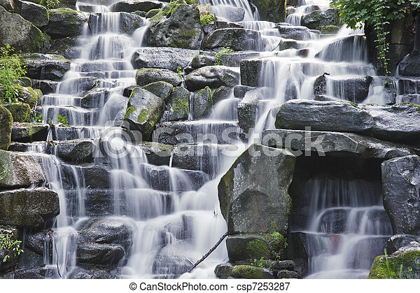 Beautiful waterfall cascades over rocks in lush forest landscape - csp7253287