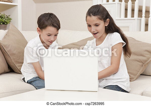 Boy & Girl Children Using Laptop Computer at Home - csp7263995