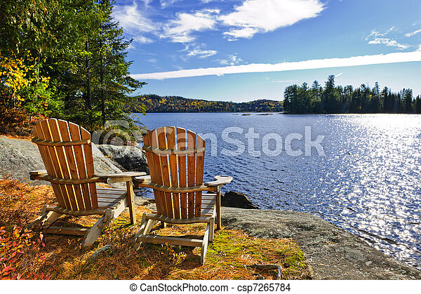 Adirondack chairs at lake shore - csp7265784