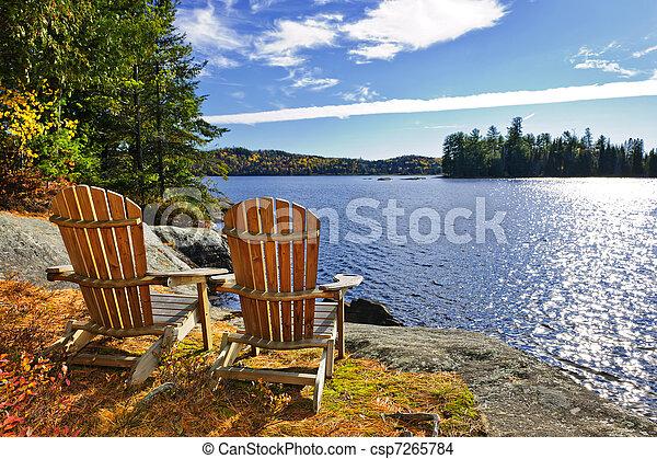 Adirondack chairs at lake shore - csp7265784
