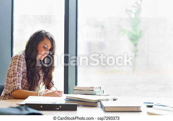 Beautiful student writing an essay - csp7293373