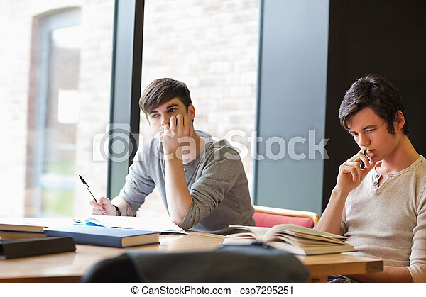 Tired young adults reviewing their notes - csp7295251