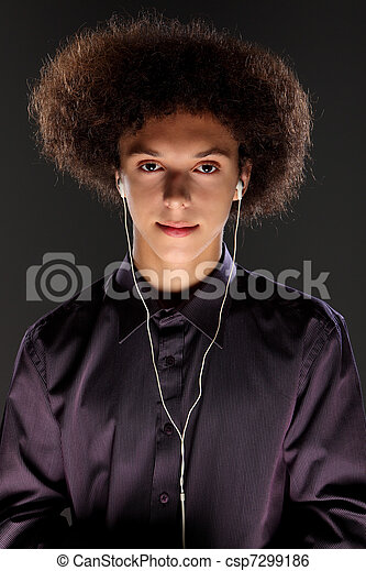 Young man wears music ear plugs and big afro hair - csp7299186
