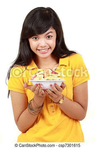 smiling teenage girl holding a bowl of cut fruits - csp7301615