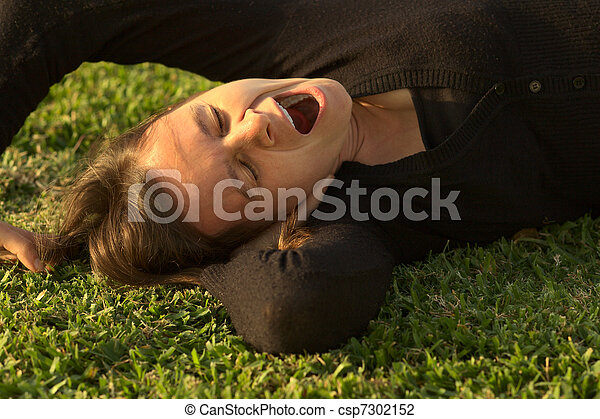 Young Caucasian woman yawning while lying on grass in a park lit by the evening light (Selective Focus, Focus on the eyes) - csp7302152