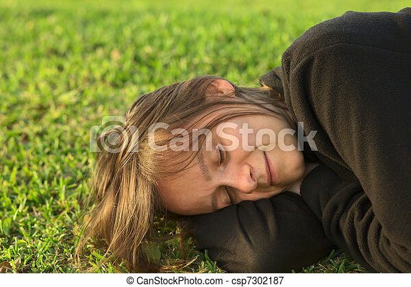 Young Caucasian woman sleeping on grass in a park lit by the evening light (Selective Focus, Focus on the left eye) - csp7302187