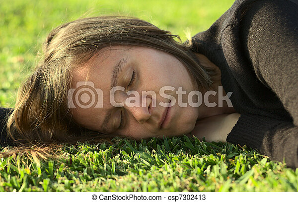 Young Caucasian woman sleeping on grass in a park lit by the evening light (Selective Focus, Focus on the left eye) - csp7302413