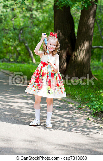 girl starts up soap bubbles on walk in park - csp7313660