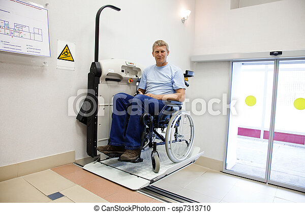 man in an invalid chair walks upstairs on the special elevating device - csp7313710