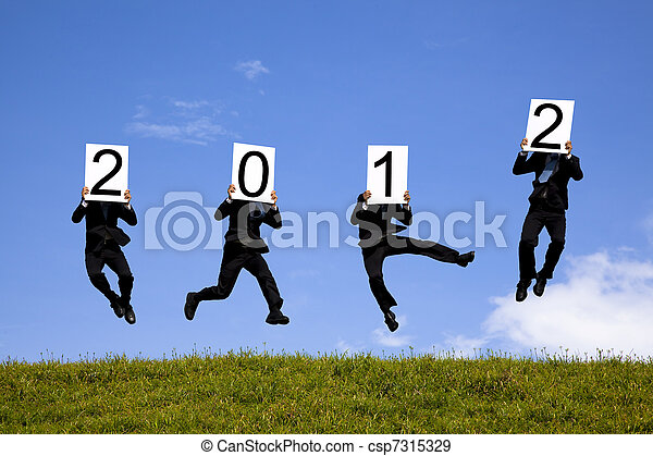 businessman holding 2012 billboard and jumping on the green field - csp7315329