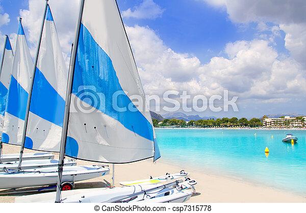 Beach of Puerto de Alcudia in Mallorca with little sailboats - csp7315778
