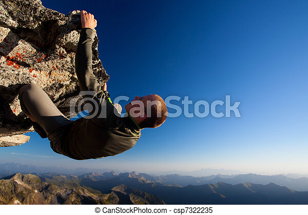 Young man climbing the rock high above mountain range - csp7322235