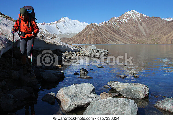Young woman with backpack on the shore of high altitude mountain lake - csp7330324