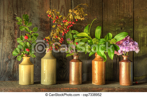 Still life image of dried flowers in rustic vase against weathered wooden background - csp7338952