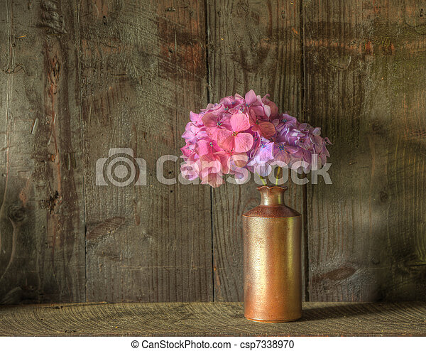 Still life image of dried flowers in rustic vase against weathered wooden background - csp7338970