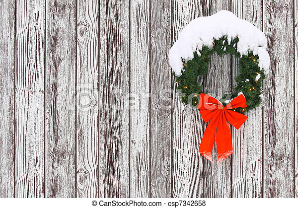 a snow covered lighted christmas wreath with a big red bow with icicles on it against a wooden pattern while it is snowing out for your use with room for your text.