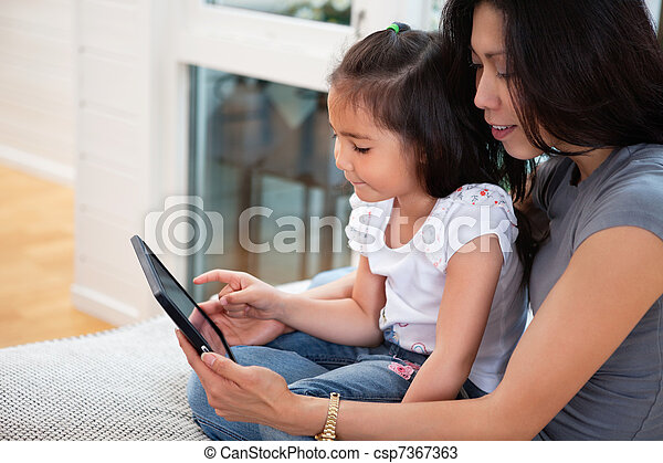 Mother and daughter reading electronic book - csp7367363