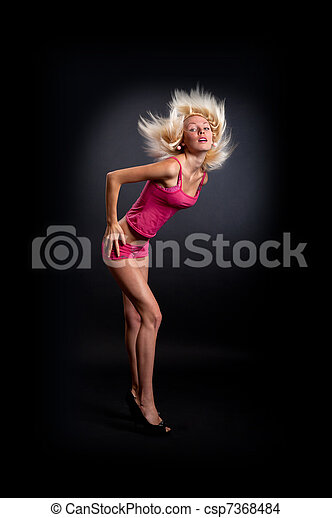 Attractive sexy woman clubbing, dancing in the disco and moving her hair isolated on a black background - csp7368484