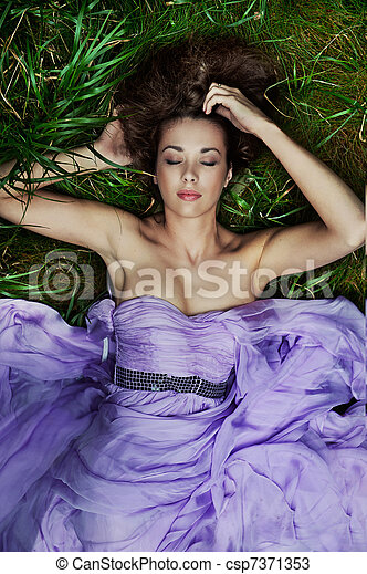 Beautiful woman laying on the grass - csp7371353