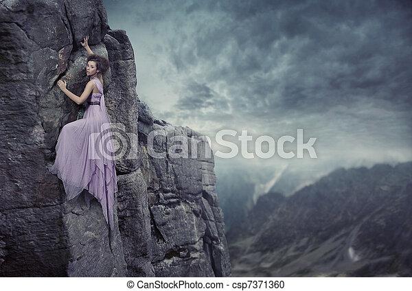 Conceptual photo of a woman climbing to the top of a mountain - csp7371360