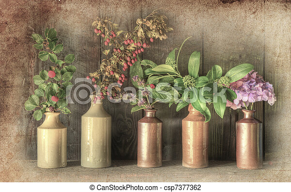 Still life image of dried flowers in rustic grunge retro vase against weathered wooden background - csp7377362
