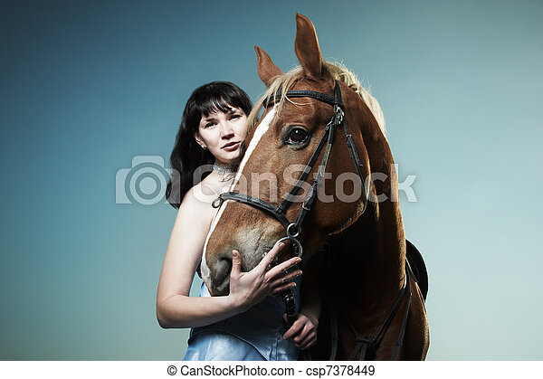 Beautiful young woman with a brown horse - csp7378449