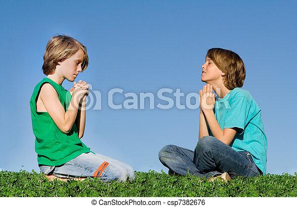 christian children praying outdoors at prayer group or bible camp - csp7382676