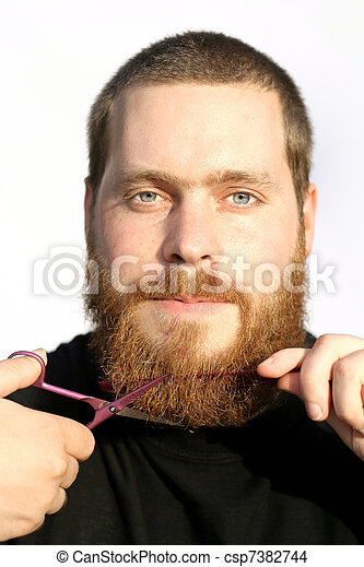 bearded man trimming or cutting beard with scissors - csp7382744