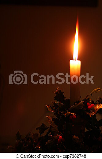 christmas holiday candle with holly decoration - csp7382748